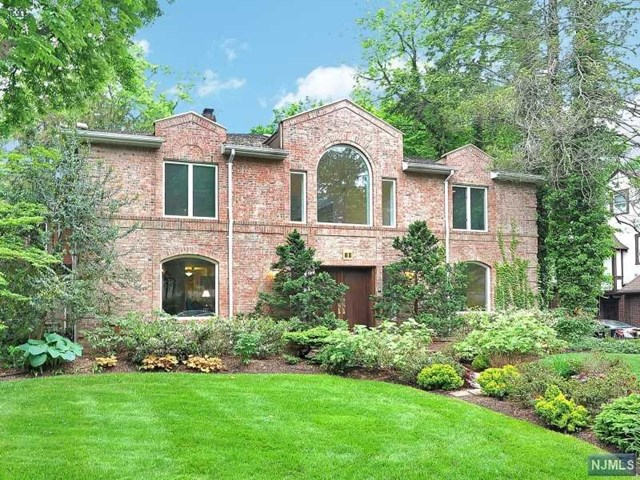 The exterior brick walls of this Colonial are not revealing the Mediterranean inspired open court yard interior style home. This house centers on the open courtyard which leads to the various large living rooms. The two story high ceilings, wrap around loggia of the second floor and large Palladium windows create a bright central focal point around which all centers. All-white walls are contrasted with dark hardwood floors accented with terracotta patterned tiles, wrought iron banisters around the upper loggia and stained glass back lit built in decorative paintings. The second floor features five very large bedrooms and three full bathrooms all around the U shaped loggia.  The basement is huge and finished with a large recreation /gaming room/ a guest room, laundry and storage. A very large backyard and Deck off the dining room and kitchen. Walk to school, NYC bus and Houses of Worship.