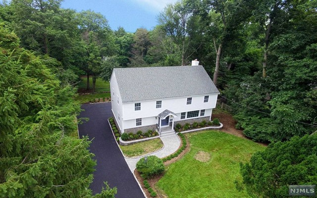 Sited On Tenafly's East Hill on a 30492 sq. ft. property. Totaly redone in 2016 Featuring 4 huge  bedrooms on the second floor with 3 full bathrooms. Large open space living room, dining room and, a family room that has slider that open to a huge new deck ovelooking the estate like property. The White kitchen features all new appliances ( Bosch, JenAir, Sharp, Kenmore ), new cabinetry and an island, has sliders to the large deck as well.  The family room features a wood burning fire place. A full refinished basement & is a walk out to the rear and opens to the two car garage. Other improvements include; new Hardie Plank siding , new driveway, new landscaping, new electric box including new electric from the street to the box, new Samsung washer/dryer, new central air handler and condenser....minutes to Maugham elementary ....