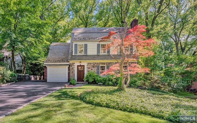 Expanded and updated colonial    on the east hill of Tenafly nestled on 1/3 acre deep property with an absolutely phenomenal backyard. Upgraded kitchen and family room open to the stone deck with fire pit and whirlpool in total privacy. First floor offers large living room with fireplace open floor kitchen with large breakfast area, formal dining room & powder room and a mud room from the attached garage. The second floor offers master bedroom w/ newer full bath, 2 large bedrooms and an updated full bath. The walk up attic is fully finished air-conditioned and heated. The full finished basement has higher ceilings and a beautiful recreation room with a f/pl, laundry area and large storage room.. Beautiful hardwood floors 1st & 2nd floor newer multi zone central air & heating, .Walking distance to NYC Bus, houses of Worship and the Excellent Tenafly Schools